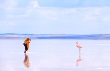 Girl taking pictures of flamingo in a salt lake Tuz Golu, Turkey