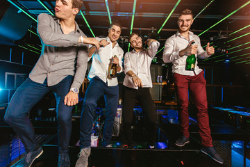 Group of smiling male friends having fun in night club