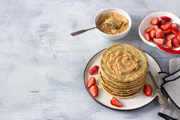 Vegan pancakes with flax seeds, peanut butter and vegan milk on a white plate on a gray background. delicious homemade healthy food