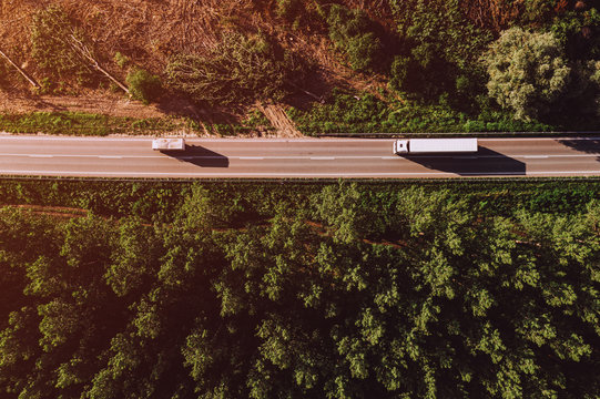 Aerial view of truck on road through forest landscape