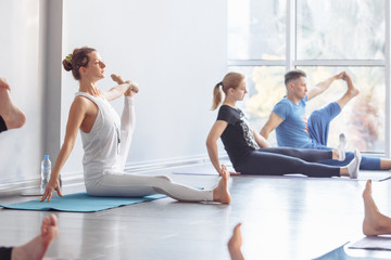 Young slim beautiful women doing pilates in spacious bright gym. ?oncept of stretching and pilates....