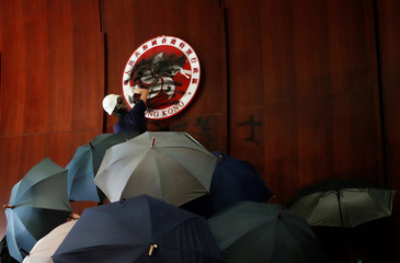 A person sprays paint over Hong Kong's coats of arms inside a chamber after protesters broke into the Legislative Council building during the anniversary of Hong Kong's handover to China in Hong Kong