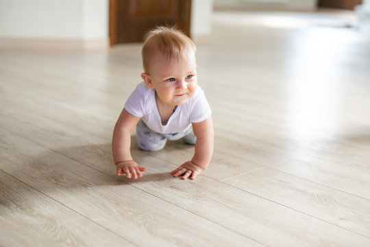 Cute little baby boy lying on hardwood and smiling. Child crawling over wooden parquet and looking up with happy face. View from above. Copyspace