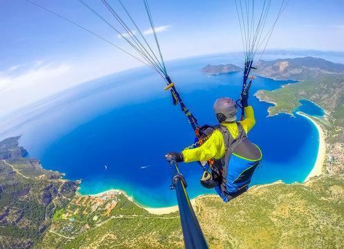 Paragliding in the sky. Paraglider tandem flying over the sea with blue water and mountains in bright sunny day. Aerial view of paraglider and Blue Lagoon in Oludeniz, Turkey.