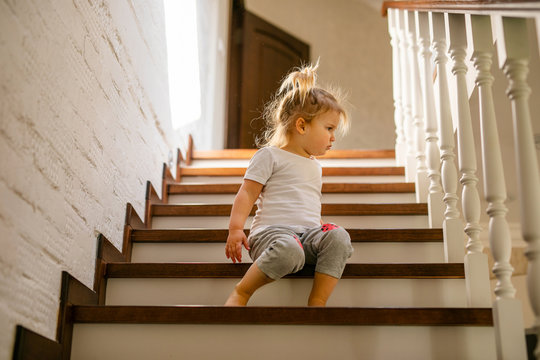 Baby blonde girl in white t-shirt at bottom of stairs indoors, looking at camera and smiling