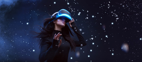 Beautiful woman with flowing hair in futuristic dress over dark background. Girl in glasses of virtual reality. Augmented reality, game, future technology concept. VR. Wall mural