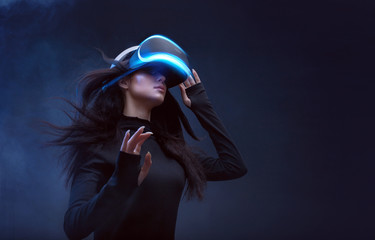 Wall Mural - Beautiful woman with flowing hair in futuristic dress over dark background. Girl in glasses of virtual reality. Augmented reality, science, future technology, robots and people concept. VR.