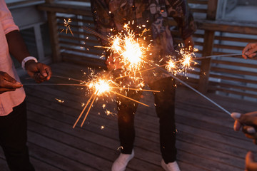 Group of friends enjoying out with sparklers in balcony