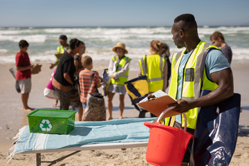 Volunteer standing with bucket and clipboard on the beach