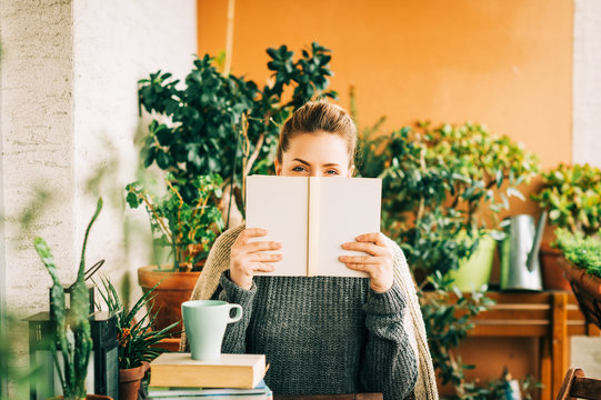 Young beautiful woman relaxing on cozy balcony, wearing warm knitted pullover, looking over the book, cup of tea or coffee on stack of books