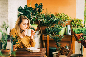 Young beautiful woman relaxing on cozy balcony, reading a book, wearing brown cotton dress, holding cup of tea or coffee