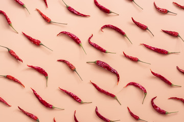 Flat lay dried red chili peppers pattern on a pink peach color background. Top view, flat lay.