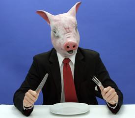 Ein Geschaeftsmann mit einer Schweinemaske sitzt  an einem Tisch ( als Symbol fuer schlechte Manieren und Tischsitten)
