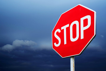 Conceptual stop sign with stormy background. Warning, caution and danger sign