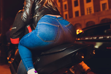 biker woman's back sitting on a motorcycle.