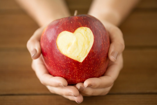 food, valentines day and health concept - close up of hands holding ripe red apple with carved heart shape over wooden table