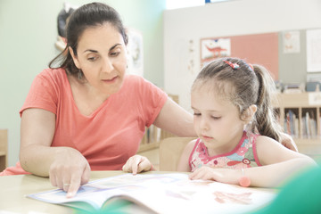 Woman teacher in a extra tutoring class with a child girl using. Empty copy space for Editor's text.