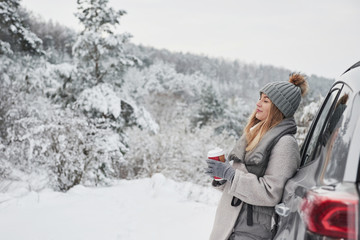 Feel the moment. Pretty girl in warm clothes standing in the winter wood while leans on the car and holding cup of coffee