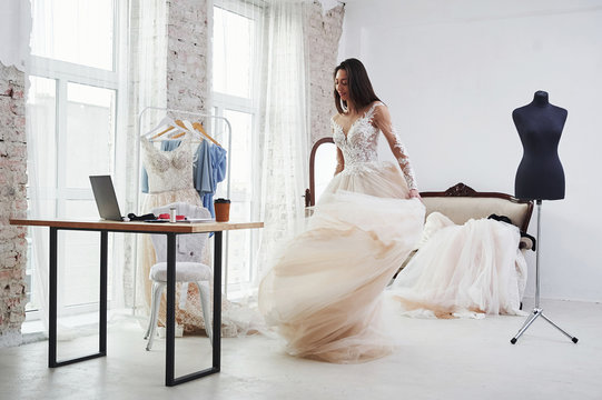 Rolling around herself. The process of fitting the dress in the studio of hand crafted clothes
