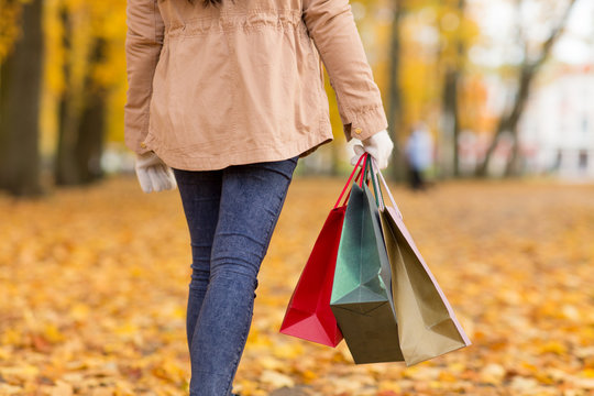 sale, consumerism, season and people concept - woman with shopping bags walking along autumn park