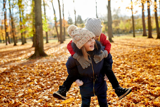 childhood, season and people concept - happy children having fun at autumn park