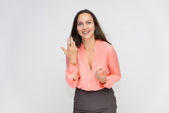 Portrait to the waist a young pretty brunette manager woman of 30 years in business clothes with beautiful dark hair. Standing on a white background, talking, showing hands, with emotions.