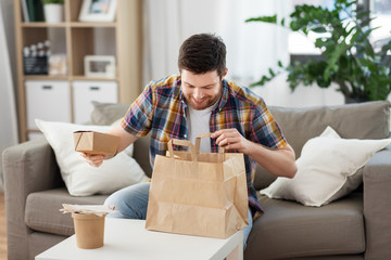 consumption, eating and people concept - smiling man unpacking takeaway food at home
