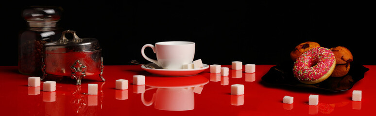 Panorama with a Cup of coffee, a donut and sugar on a red glossy table