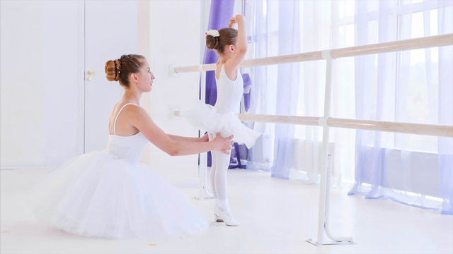 Personal ballet lesson for little girl. Professional teacher is training a little girl standing near the barre stand in ballet class, side view. They both are in white tutus and pointes.
