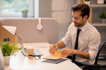 Content white-collar man opening notepad