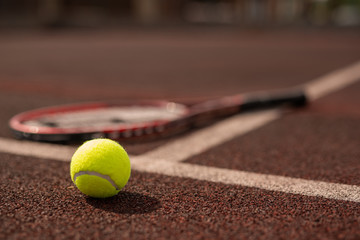 Yellow tennis ball on sports playground and tennis racket