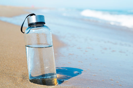 reusable water bottle on the beach