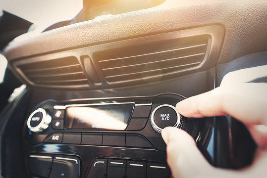 Man turning on car air conditioning system