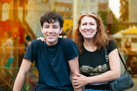 Guy of adolescence with his mother talk, laugh, have fun together all evening at sunset in the summer