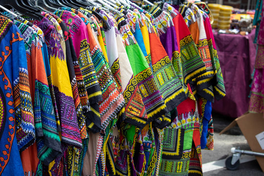 A rack of colorful dashikis displayed on hangers at an outdoor market.