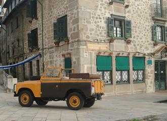Esquina de predio antigo com automóvel antigo parado, foto nostálgica - 4x4
