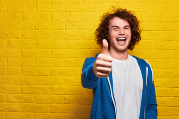 Cheerful young man showing thumb up
