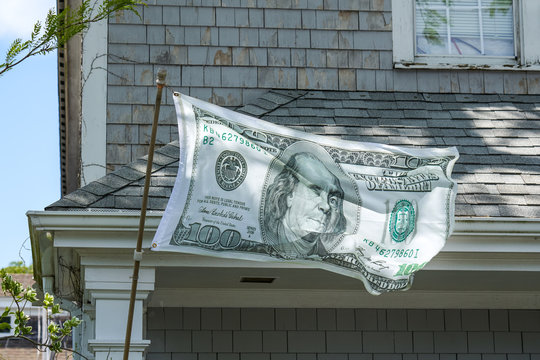 Ben Franklin appears to be winking on a one hundred dollar bill flag waving in the wind on a pole in front of a house