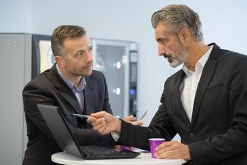 suited men looking at laptop during coffee break