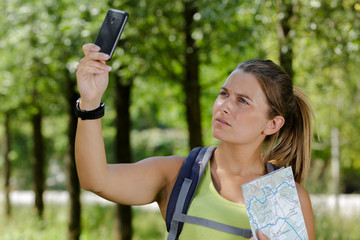 woman wearing backpack holding her smartphone in the air