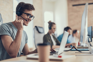 Happy guy in glasses is working in the call center