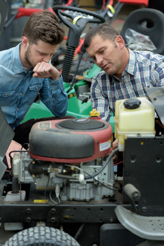 mechanics examining mower engine