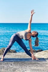 Beautiful young woman practicing yoga on seaside against blue sea.