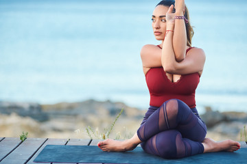 Portrait of beautiful young woman making yoga exercises on seaside against blue sea.