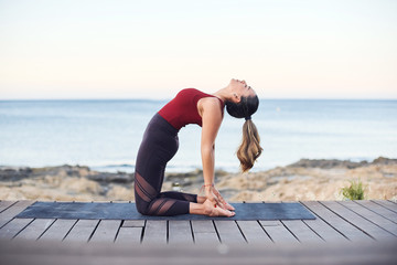 Young attractive woman practices yoga in camel pose on the beach. Wall mural