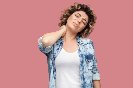 Neck or back pain. Portrait of young woman with curly hairstyle in casual blue shirt standing and holding her painful neck and feeling bad. indoor studio shot, isolated on pink background.