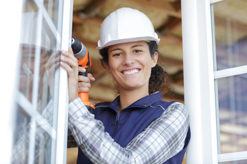 woman builder using a drill for fixing a window