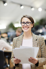 Waist up portrait of smiling businesswoman posing in office holding documents