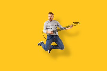 Jumping young man with drawn guitar on color background