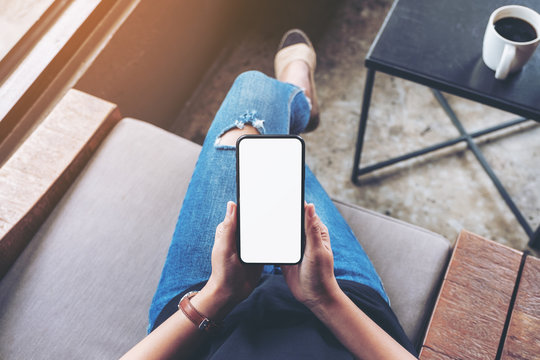 Top view mockup image of woman holding black mobile phone with blank screen while sitting in cafe